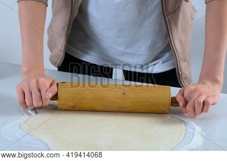 Woman Is Rolling Dough For Dumpings Using Rolling Pin On Table, Hands Closeup.