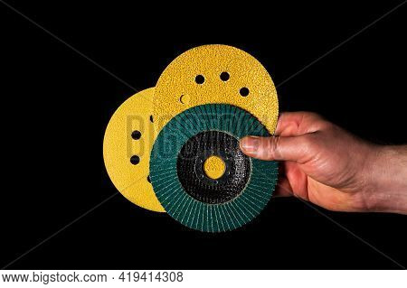 Builder Hand Keeps Or Gives Abrasive Tools Close Up On Isolated Black Background. The Idea Of Starti