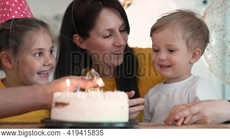Birthday. Happy Family On Holiday Party. Parents And Childs With Baby Getting Ready To Blow Out Birt