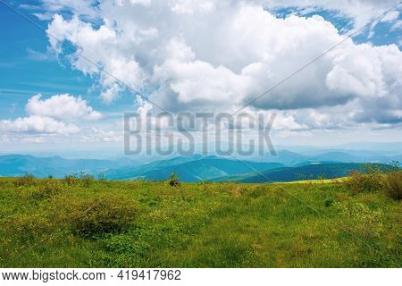 Grassy Alpine Meadow On The Edge Of Hill. Beautiful Summer Landscape In Mountains. Clouds Above The