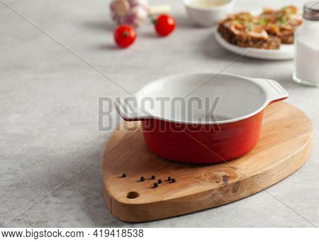An Empty Red Bowl On A Wooden Chopping Board For Soup, Slices Of Bread With Salted Pork Bacon Or Lar