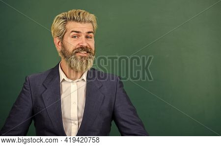 Introduced And Welcomed By University. Teacher Explain Topic. Man Teacher In Front Of School Chalkbo
