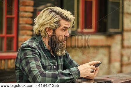 Application Concept. Bearded Hipster Man Hold Smartphone Building Background. Messaging Online. Mode