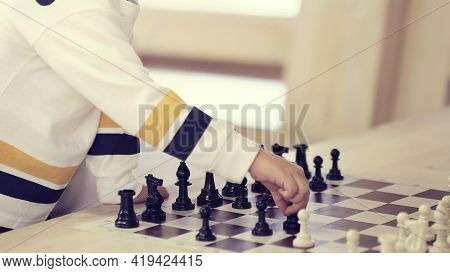 Little Child Plays Chess. Child Hand Making Right Move