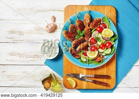 Lamb Kofta Kebabs Of Ground Lamb, Served On A Blue Plate With Yogurt Dressing, Fresh Vegetables Sala