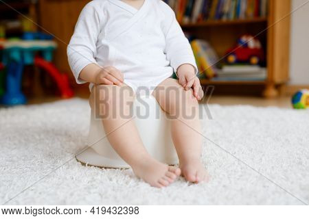 Closeup Of Cute Little Old Toddler Baby Girl Child Sitting On Potty. Kid Playing With Educational To