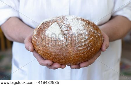 Baker Woman Holding Homemade Rustic Wheat Bread. Selective Focus. Bread In Old Wrinkled Hands Of Gra