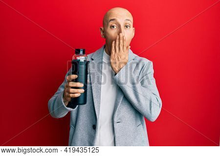 Bald business man with beard drinking bottle of water covering mouth with hand, shocked and afraid for mistake. surprised expression