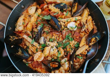 Classic Dish Of Spain, Seafood Paella In Traditional Pan On Rustic Wooden Background Top View. Spani