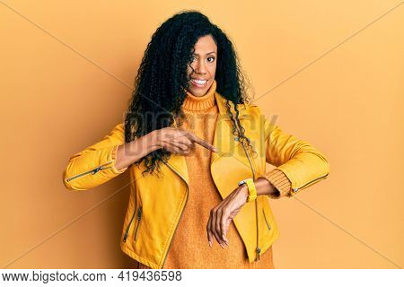 Middle age african american woman wearing wool winter sweater and leather jacket in hurry pointing to watch time, impatience, upset and angry for deadline delay