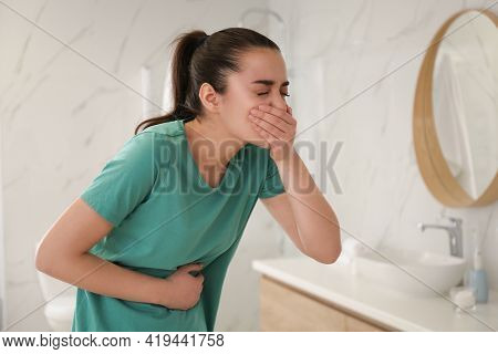 Young Woman Suffering From Nausea In Bathroom. Food Poisoning