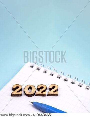 Banner 2022 And Notepad. Figures 2022 On Blue Background. Wooden Figures On Blue Background. New Yea