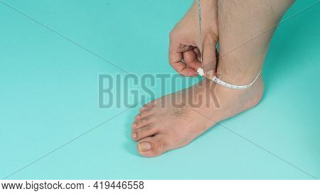 Tape Measure In Hands With Barefoot And Legs On Mint Green Color Or Tiffany Blue Background.