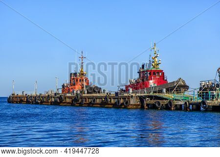 Sea Boats At Their Own Pier As They Looks From Embankment. Shot In Kerch, Crimea