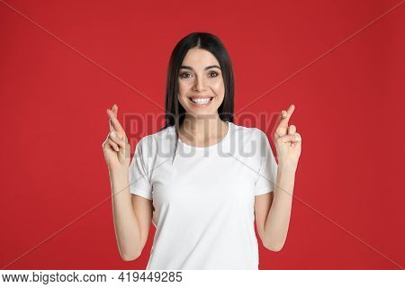 Woman With Crossed Fingers On Red Background. Superstition Concept