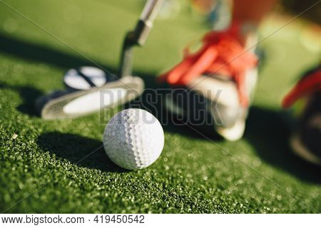 Kids Play Mini Golf. Close-up Image Of Player In Snickers With Mini Golf Club And White Golf Ball. E