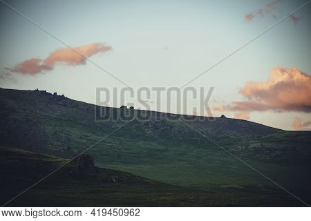 Minimalist Mountain Landscape With Orange Clouds In Sunset Sky Above Green Hills With Rocks. Atmosph