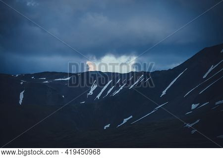 Dark Atmospheric Silhouette Of Rocky Mountain Wall Under Dusk Cloudy Sky In Phantom Blue Color. Awes