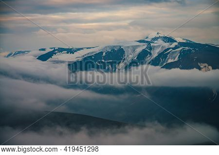 Scenic Foggy Mountain Landscape With Great Snowy Mountain Range In Sunlight Above Big Low Clouds Sun