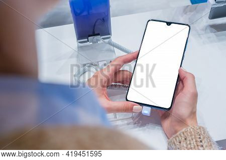 Mockup Image: Woman Customer Testing New Model Of Smartphone With Blank White Display At Electronic