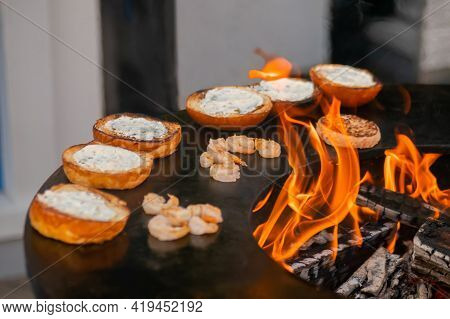Process Of Preparing Fish Burgers With Shrimp, Prawn On Brazier With Hot Flame At Summer Local Food