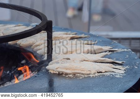 Process Of Cooking European Smelt Fish In Flour On Black Brazier At Summer Outdoor Food Market: Clos