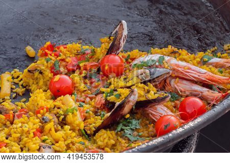 Cooked Paella With Shrimp, Mussel, Rice, Cherry Tomato In Huge Paella Pan At Summer Outdoor Food Mar