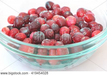Frozen Cowberry And Cherries In A Glass Plate On A White Background. Close-up Of Berries Covered Wit