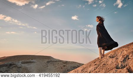 Attractive brunette woman in a black dress looks into the distance in the desert. Fashion shot in nature. View of the desert and the sky.