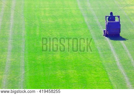 Lawn Mower At The Stadium . Football Stadium Before The Game . Grass Terrain For Sport Games