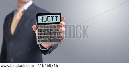 Word Audit On Calculator. Businessman Shows Calculator With Word Audit On Screen. Tax, Accounting, S