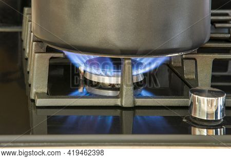 A Cooking Pot Sits On A Natural Gas Burner On The Top Of A Hob