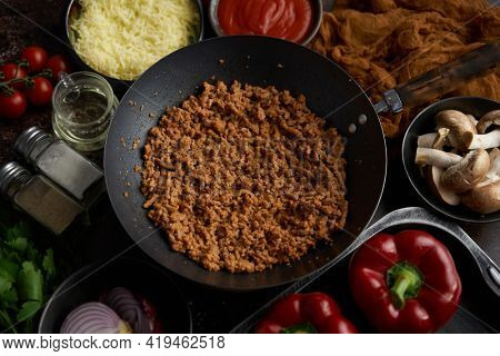 Ingredients on a table prepared for stuffing peppers. Red bell peppers, minced meat, cheese