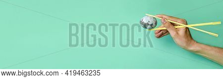 A Space Egg In The Hands Of A Young Man With Japanese Chopsticks On A Neon Background. Minimal Easte