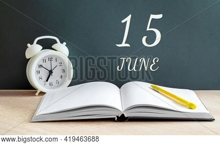 June 15. 15-th Day Of The Month, Calendar Date.a White Alarm Clock, An Open Notebook With Blank Page