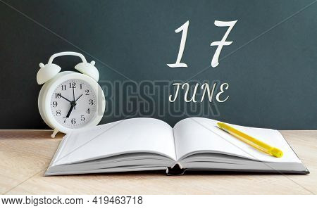 June 17. 17-th Day Of The Month, Calendar Date.a White Alarm Clock, An Open Notebook With Blank Page