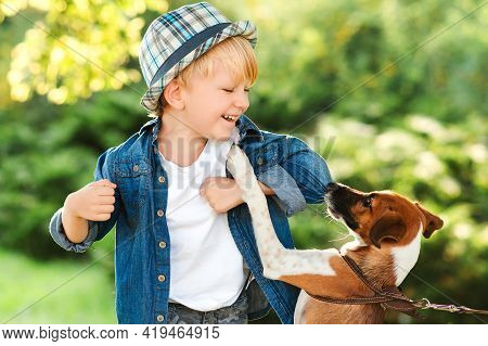 Happy Child Having Fun Together With Dog Outdoors. Little Puppy Jack Russel Terrier Playing With Boy