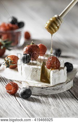 Camembert Cheese With Honey, Raspberries, Blueberries And Strawberries. Honey Flowing With Honey Sti