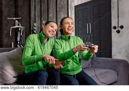 Cybersports Women Train Before Competition, Sitting On Couch In Loft Apartment With Joystick In Hand