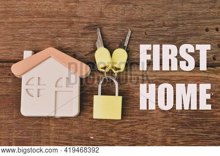 Top View Of Toy House, Padlock And Keys Over Wooden Background Written With First Home.