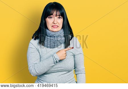 Young hispanic plus size woman wearing winter scarf pointing aside worried and nervous with forefinger, concerned and surprised expression