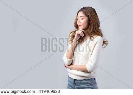 Asian Woman Closed Her Eyes While Touch Her Chin For Thinking Expression On Grey Background. Concept