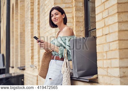 Waist Up Shot Of Attractive Woman With Shopping Bags