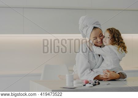 Young Mom And Little Daughter In White Bathrobes Hugging While Doing Hygiene Or Spa Procedures Toget