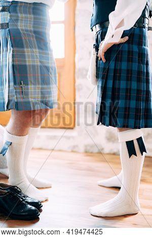 Preparing For A Scottish Wedding. Two Men In Kilts, Sporrans And High Socks Stand Opposite Each Othe