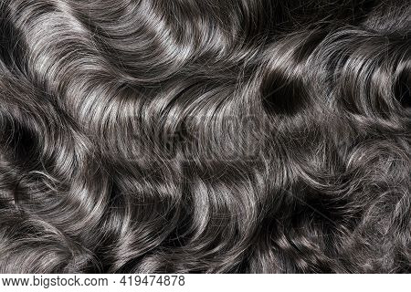 Black Hair Texture. Wavy Long Curly Dark Hair Close Up As Background. Hair Extensions, Materials And