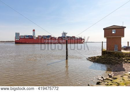 Stade, Germany – April 16, 2021: Reefer container ship CAP SAN MARCO, operated by shipping company HAMBURG SÜD, passing Stadersand stream gauge station on Elbe river heading to Hamburg.