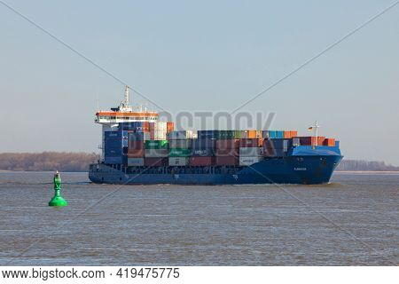 Stade, Germany – April 16, 2021: Feeder ship ELBWATER, a small container ship, on Elbe river heading to Hamburg.