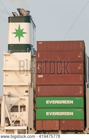 Stade, Germany – March 31, 2021: Chimney and stacked containers, detail of Container ship EVER GLORY, owned by Evergreen Marine Corp. (Taiwan) Ltd.