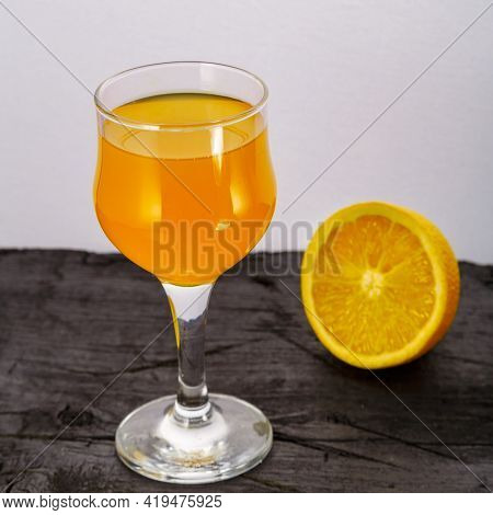 Orange Juice In A Glass Near Oranges On A Black Background. Square Photo
